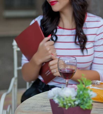 Pretty brunette woman in a striped t-shirt holding a magazine and drinking red wine in outdoor cafe Фото со стока - 129841165