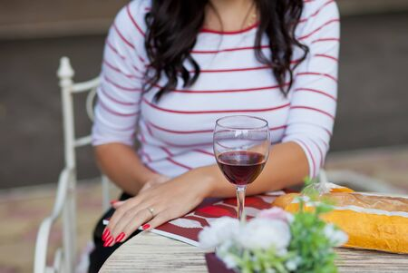 Pretty brunette woman in a striped t-shirt drinking red wine in outdoor cafe Фото со стока - 129841163