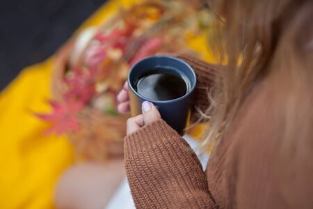 Outdoors autumn picnic. Young woman holding mug of hot coffee in a hand. Stockfoto
