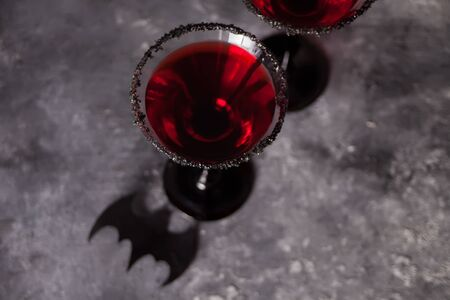 Two glasses with red cocktail for Halloween party on the dark background.