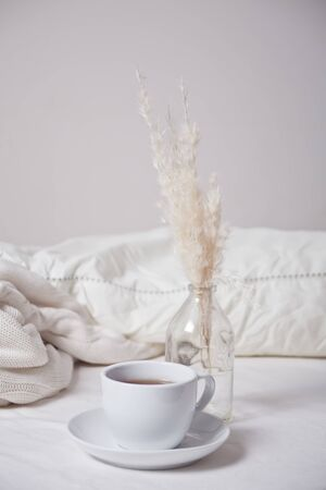 Close up of cup of tea, bouquet of white dry flowers in the bed. Summer romantic morning. Top view. Stock Photo
