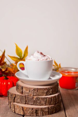 Cup of hot creamy cocoa with froth with autumn leaves and pumpkins on the background. Zdjęcie Seryjne