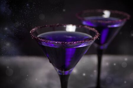 Two glasses with purple cocktail for Halloween party on the dark background. Top view.