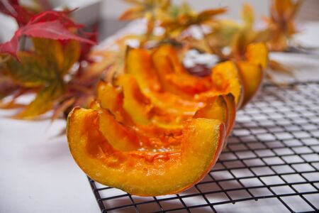 Fresh pumpkin cut in pieces of a oven metal baking rack with herbs and spices with colorful autumn leaves on the background. Stok Fotoğraf