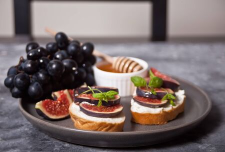Sandwich with cream cheese, figs and honey served on the gray plate on the concrete background. Healthy food concept.