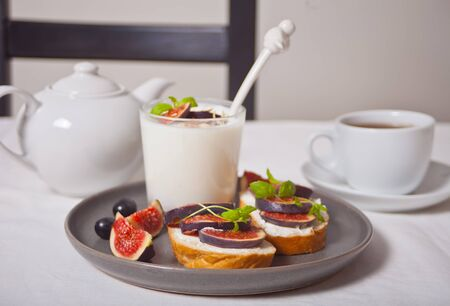 Yogurt with muesli and fig fruit, sandwich with cream cheese, figs and honey on the white tray. Healthy breakfast food concept.