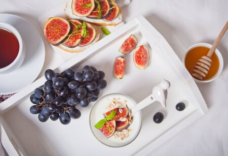 Yogurt with muesli and fig fruit, sandwich with cream cheese, figs and honey on the white tray. Healthy breakfast food concept. Top view. Stock Photo