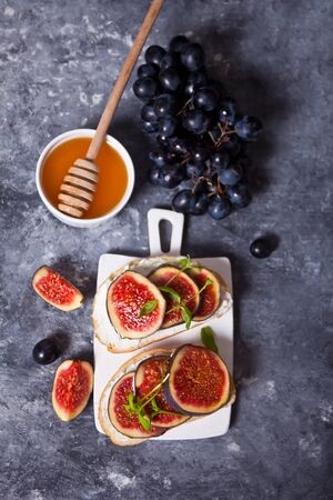Sandwich with cream cheese, figs and honey served on a small white cutting board. Healthy food concept. Top view.