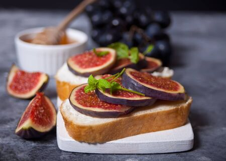 Sandwich with cream cheese, figs and honey served on a small white cutting board. Healthy food concept. Stock Photo
