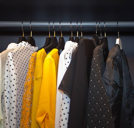Different clothes hanging on a rack. Stock Photo