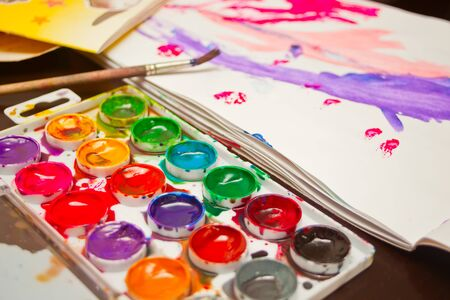 Durty watercolors with eighteen colors with brush and album on a table.