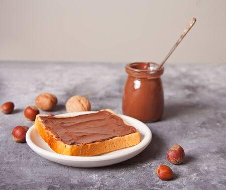 Brottoast mit Schokoladencreme auf dem konkreten Hintergrund.