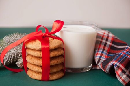 Glass of milk, cookies and pine branch on the green table. Stock Photo