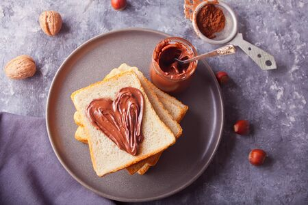 Bread toast with chocolate cream, jar of chocolate cream on the concrete background. Top view.