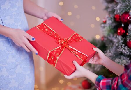 Woman give a child Christmas red gift box with Christmas tree on the background