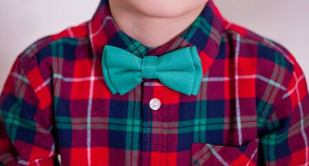 Boy weared in red checkered shirt and tie butterfly. New year eve. Christmas fashion.