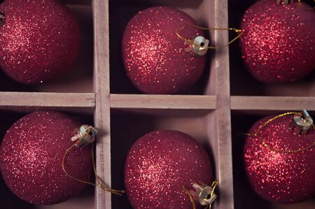 Red Christmas sparkle balls in a wooden box.