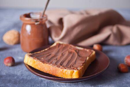 Bread toast with chocolate cream, jar of chocolate cream on the concrete background.