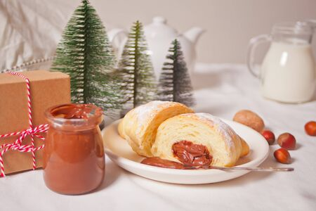 Fresh croissants bun with chocolate on the plate, cup of coffee, jar of milk nearby, three little Christmas tree toy and gift box on the white background