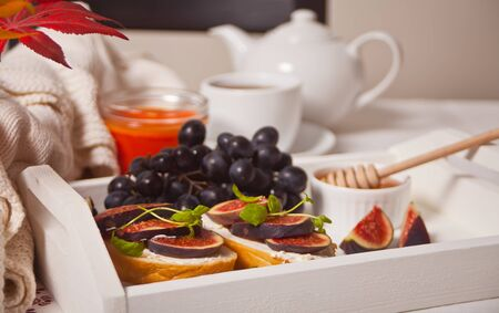 Sandwiches with cream cheese, figs and honey on the white tray. Healthy breakfast food concept.