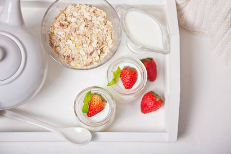 Two portions natural homemade yogurt in a glass jar with fresh strawberry and muesli nearby. Imagens