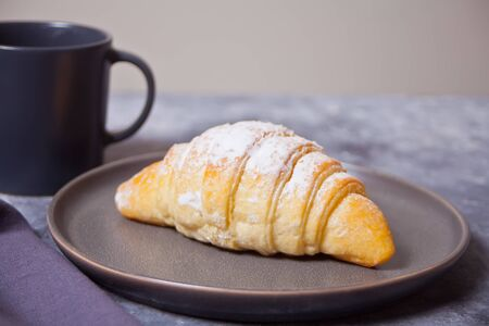 Fresh croissants buns on the gray plate and cup of coffee nearby