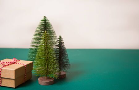 Christmas gift box on the blue background with three small Christmas tree toys. Copy space.