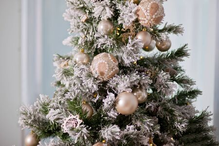 Decorated Christmas tree on light background.