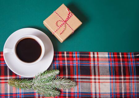 Cup of coffee, gift box, pine branch on the green background with checkered napkin. Top view.