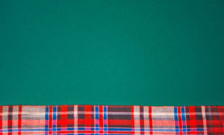 Checkered napkin on the green background. Top view. Copy space
