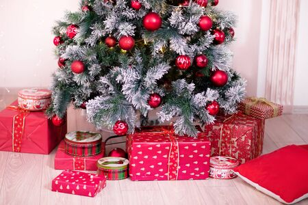 Decorated Christmas tree with many gift boxes nearby. Imagens