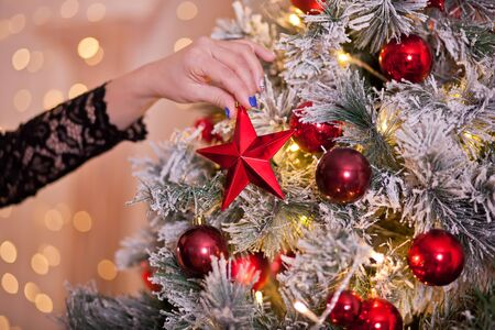 Womans hand holding a Christmas decor big red star in a hands on the Christmas tree background. Imagens