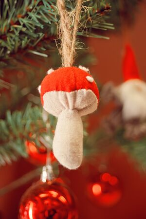 Decorated Christmas tree and hanging small fly agaric mushroom.