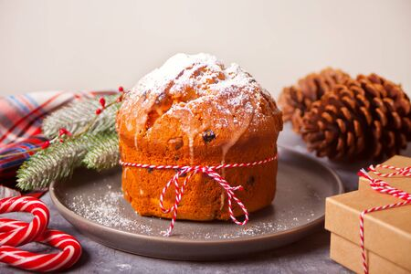 Traditional Christmas cake panettone with fruits and nuts with Christmas decoration. Imagens