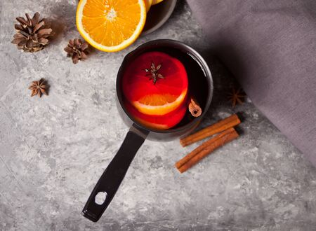 Old metal pan pot of tasty mulled wine with pot with spices and orange fruits and gift boxes on wooden table. Top view.