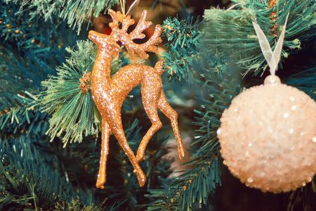Decorated Christmas tree and hanging small white ball and deer.