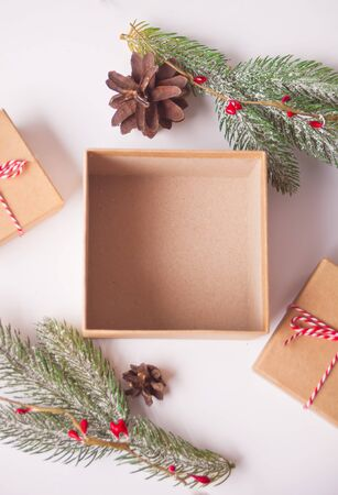 Opening and empty Christmas gift box on the blue background with pine branch and Christmas decoration.