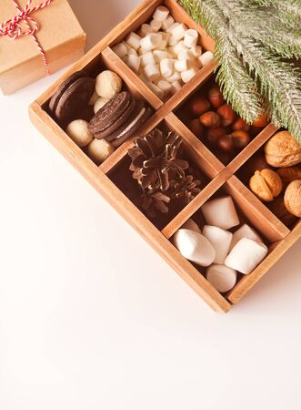 Christmas wooden box with marshmallows, cookies and nuts. Top view. Copy space. Imagens