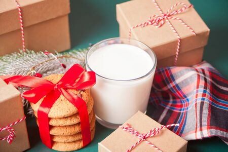 Glass of milk, cookies, Christmas gift boxes and pine branch on the green table.