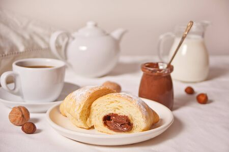 Fresh croissants bun with chocolate on the plate, cup of coffee, jar of milk nearby on the white background.