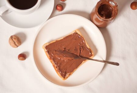 Bread toast with chocolate cream, jar of chocolate cream on the white background. Top view.