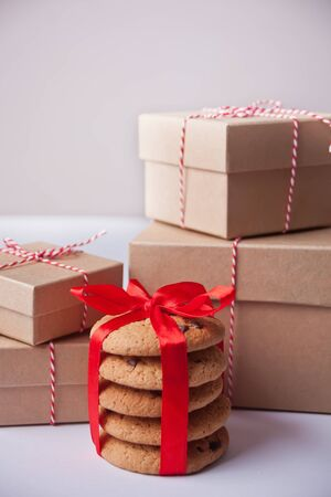 Different sizes Christmas gift boxes, homemade cookies for present on the light background.