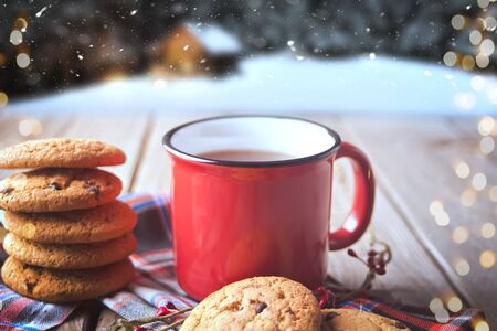 Cookies with red mug of hot tea or coffee on the wooden table with winter landscape on the background. Imagens