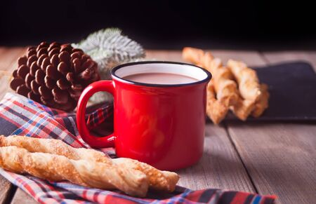 Bread sticks with red mug of hot tea or coffee on the wooden table.
