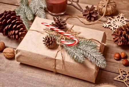 Gift box and Christmas decor on the wooden table. Christmas present decoration. Handmade decor concept.