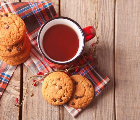 Cookies with red mug of hot tea or coffee on the wooden table. Top view. Copy space.