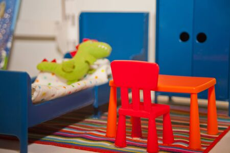 Life of a little dinosaur. Dinosaur sleeping in bed. Near a table, chair and wardrobe Imagens