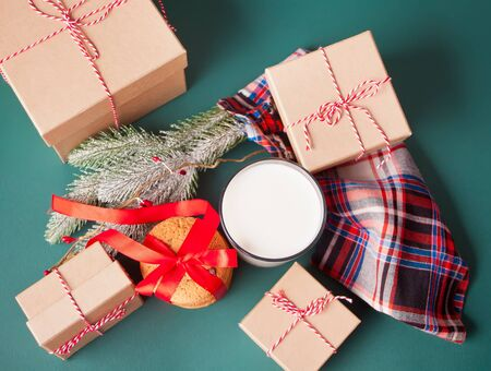 Glass of milk, cookies, gift boxes and pine branch on the green table. Christmas concept Imagens