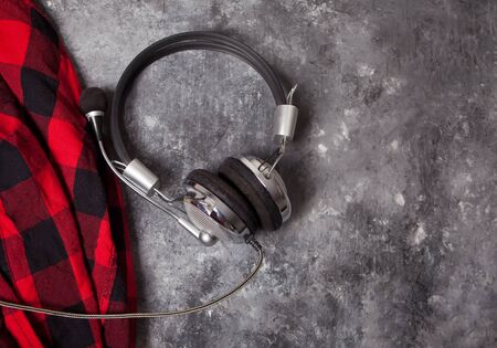 Headphone music and warm checkered shirt or plaid on the gray background. Lifestyle, music concept. Top view. Copy space.