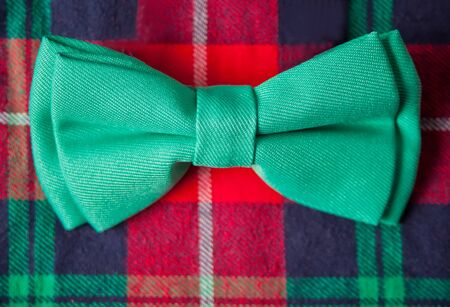 Red checkered shirt and green butterfly for party. New year eve. Christmas fashion. Close up.